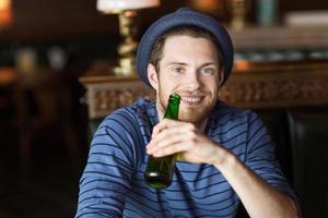 glücklicher junger Mann, der Bier an der Bar oder im Pub trinkt foto