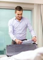 Geschäftsmann packt Sachen in Koffer foto