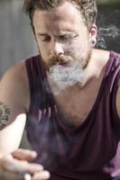 Nahaufnahme des Mannes, der auf der Treppe raucht foto