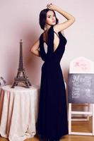 schöne Frau mit luxuriösem lockigem Haar im eleganten schwarzen Kleid foto