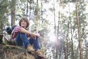 lächelnder männlicher Wanderer, der weg schaut, während er auf Klippe sitzt