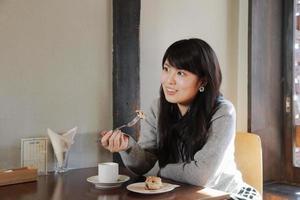 Frau, die Kuchen im japanischen Café isst foto