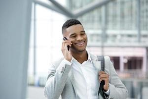 junger schwarzer Mann, der mit Handy lächelt foto