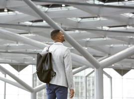 schwarzer Mann, der allein im Flughafen mit Tasche steht