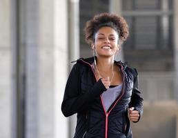 lächelnde junge Frau, die draußen mit Kopfhörern läuft