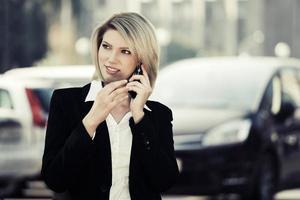 Modegeschäftsfrau, die das Telefon im Freien anruft foto