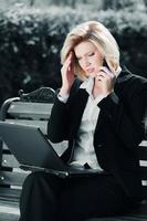 müde Geschäftsfrau, die auf dem Handy anruft foto