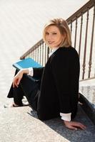 glückliche Geschäftsfrau mit einem Ordner, der auf den Stufen sitzt foto