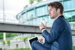 Geschäftsmann, der draußen sitzt und Kaffee trinkt und arbeitet foto