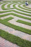 Frau mit Laptop in einem Kopfsteinpflaster Labyrinth foto