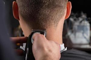 Friseur schneidet Kunden Haare mit einem elektrischen Haarschneider foto