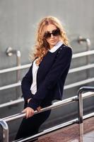 junge Modegeschäftsfrau, die auf der Stadtstraße geht foto