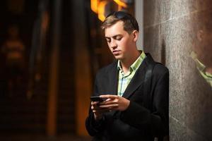 junger Mann mit einem Handy, das an der Wand steht foto