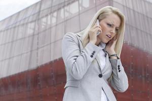 frustrierte Geschäftsfrau im Anzug auf Handy gegen Bürogebäude