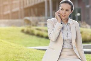 schöne junge Geschäftsfrau, die auf Handy unterhält, während sie wegschaut foto