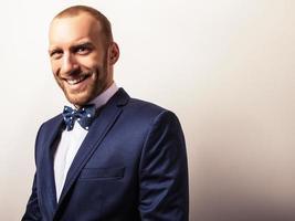 eleganter junger hübscher Mann im dunkelblauen Kostüm. foto