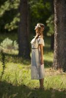 hübsche junge Boho-Frau, die im Wald steht foto