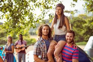 hübscher Hipster auf den Schultern von Freunden foto