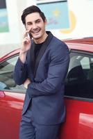 junger Geschäftsmann, der mit seinem Handy nahe einem Auto spricht foto