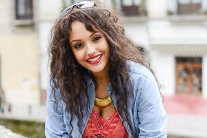 attraktive gemischte Frau im städtischen Hintergrund, die lässige Kleidung trägt foto