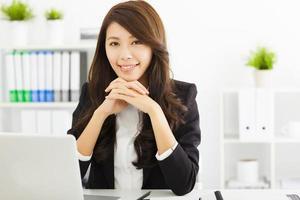 lächelnde junge Geschäftsfrau, die im Büro arbeitet foto