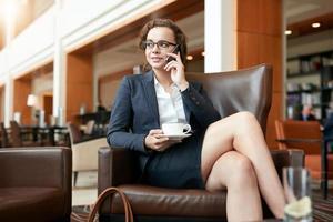 Geschäftsfrau, die im Café sitzt und auf Handy spricht foto