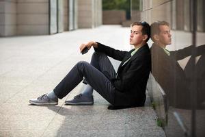 junger Mann mit einem Handy, das an der Wand sitzt foto