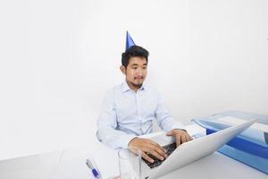 Geschäftsmann, der Partyhut trägt, während Laptop im Büro verwendet wird foto