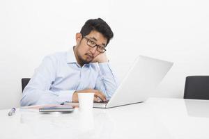 gelangweilter Geschäftsmann, der mit Laptop am Schreibtisch im Büro sitzt foto