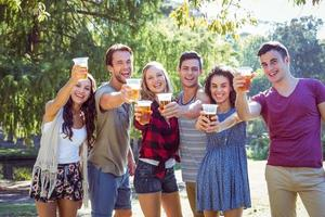 glückliche Freunde im Park, die Bier trinken foto