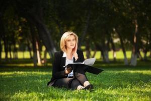 junge Geschäftsfrau mit einem Ordner in einem Stadtpark