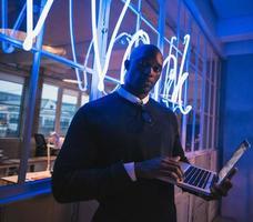 junge Führungskraft, die im Büro mit einem Laptop steht foto