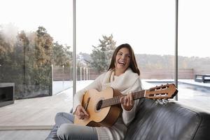 Frau spielt Gitarre im Wohnzimmer foto