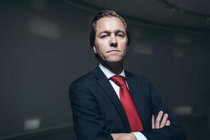 ernsthafter selbstbewusster Geschäftsmann mit roter Krawatte im Raum. foto