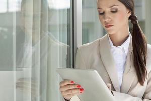 schöne Geschäftsfrau mit digitalem Tablet durch Glastür