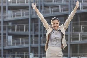 aufgeregte junge Geschäftsfrau mit erhobenen Armen, die gegen Bürogebäude stehen foto