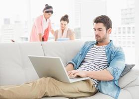 fokussierter Geschäftsmann mit Laptop auf Sofa foto