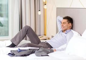 glückliche Geschäftsfrau, die im Bett im Hotelzimmer liegt