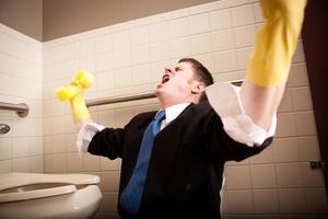 wütender, schreiender Geschäftsmann, der die Toilettentoilette putzt foto