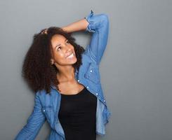 glückliche junge Frau, die mit Hand im Haar lächelt foto