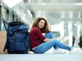 Frau lächelt mit Tasche am Bahnhof foto