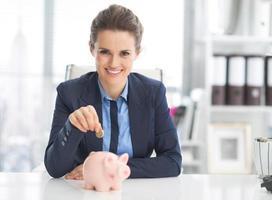 glückliche Geschäftsfrau, die Münze in Sparschwein setzt foto