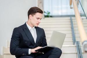 Loyalität zur Arbeit. selbstbewusster Geschäftsmann, der auf der Treppe sitzt foto