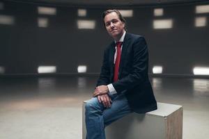 junger zufriedener Unternehmer, der auf Holzkiste im leeren Raum sitzt. foto