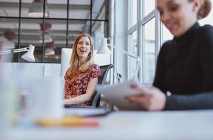junge Frau, die freundschaftliches Gespräch mit ihrem Kollegen hat foto