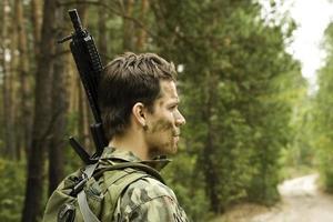 Airsoft-Spieler, Mann in Tarnung mit Waffe foto