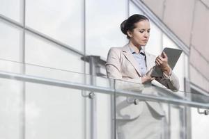 schöne junge Geschäftsfrau, die digitales Tablett am Bürogeländer verwendet foto