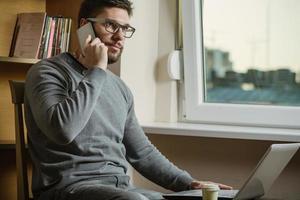 junger Geschäftsmann, der Handy im Büro benutzt foto