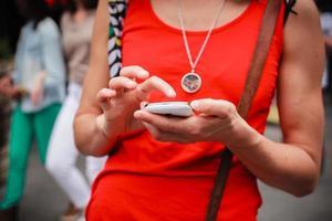 junge Frau, die in der Straße mit ihrem Telefon steht foto