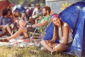 sorgloser Hipster, der auf Campingplatz lächelt